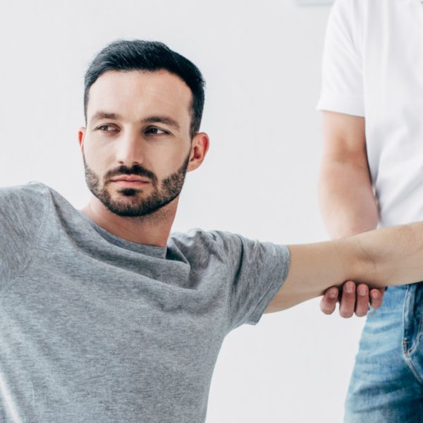 panoramic shot of chiropractor stretching arm of handsome patient with dumbbells in hospital